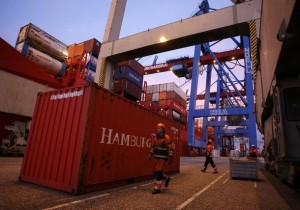 Workers walk around a container at the Container terminal Burchardkai at Hamburg harbour late January 14, 2008. The Burchardkai terminal of the Hamburger Hafen und Logistik AG (HHLA) is the largest container handling facility in the Port of Hamburg.  REUTERS/Christian Charisius (GERMANY)